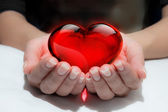 Glass heart in the heart hand — Stock Photo
