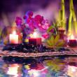 composición violeta - velas, aceite, orquídeas y bambú en agua — Foto de Stock
