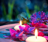Dish spa with 2 floating candles, orchid on mat — Stock Photo