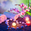 Stock Photo: Heart of stones massage with candles, orchids, towels and bamboo