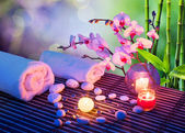Heart of stones massage with candles, orchids, towels and bamboo — Stock Photo