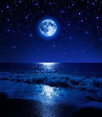 Super moon in starry sky on sea beach — Stock Photo