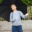 Teenage boy with umbrella waiting for rain — Stock Photo #30481595