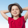 Cute little girl outside wearing a red shirt and a hat — Stock Photo
