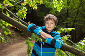 Teenage Boy leaning on a trunk. — Stockfoto