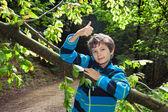 Adolescente, apoyado en un tronco, pulgar hacia arriba. — Foto de Stock