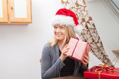 Blond Woman wearing a red santa hat — Stok fotoğraf