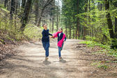 Brother and Sister running in a forest hand in hand — Stock Photo
