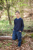 Good looking boy standing in a forest — Stock Photo