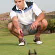 Male golfer crouching while aiming at ball — Stock Photo