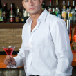 Man in a pub with red martini — Stock Photo