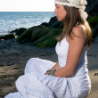 Girl in white dress sitting at the beach — Stock Photo #30772041
