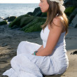 Girl in white dress sitting at the beach — Stock Photo #30772043