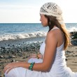 Girl in white dress sitting at the beach — Stock Photo