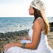 Girl in white dress sitting at the beach — Stock Photo #30772049