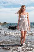 Blonde woman walking by the seaside — Stock Photo
