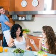 Women enjoying her salad and man in the kitchen — Stock Photo