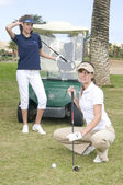 Two beautiful woman playing golf — Stock Photo
