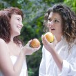 Young women eating an apple — Stockfoto