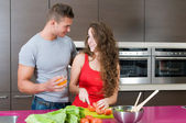 Couple in the kitchen with salad — Stock Photo