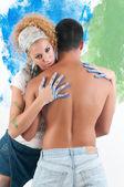 Abrazo de la pareja mientras pinta — Foto de Stock