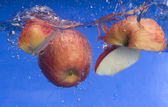 Fresh apple falling in water — Stock Photo