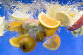 Fresh fruit splashing in fresh water — Stock Photo