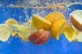Fresh fruit falling in water — Stock Photo