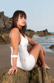 Sexy woman sitting on rocks — Stock Photo