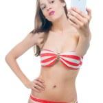 Beautiful woman in bikini  taking picture on her phone — Stock Photo #47307391