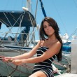 Young beautiful girl pulls the rope with a yacht on the quay — Stock Photo #47584157