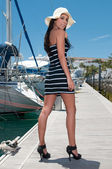 Pretty young girl posing against yachts in the quay — Stock Photo
