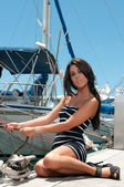 Young beautiful girl pulls the rope with a yacht on the quay — Stock Photo
