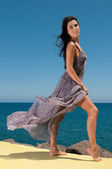 Beautiful girl in a long dress on the beach — Stock Photo