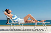 Young beautiful girl in a bathing suit on a sun lounger — Stock Photo