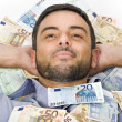 Happy Young Man laying on Banknotes — Stock Photo