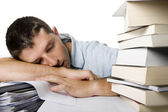 Young Man Overwhelmed sleeping over a pile of books — Stockfoto