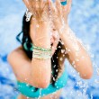 Woman splashing water at the beach — Stock Photo