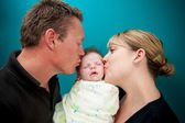 Father and Mother Kissing their baby — Stock Photo