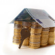 Euro Coins pile House with banknote roof and key — Stock Photo