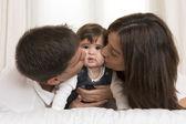 Madre y padre besando a hija — Foto de Stock
