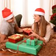 Young Happy Couple on rug at Christmas with Presents — Stok fotoğraf