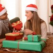 Young Happy Couple on rug at Christmas with Presents — Stock Photo #35081545
