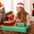 Young Happy Couple on rug at Christmas with Presents — Стоковое фото