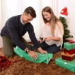 Young Happy Couple wrapping Christmas presents — Stock Photo #35081641