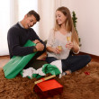 Young Happy Couple opening Xmas presents — Stock Photo #35081661