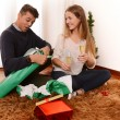 Young Happy Couple opening Xmas presents — Stock Photo #35081827