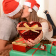 Young Happy Couple Kissing on rug at Christmas — Stock Photo #35081929