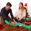 Young Happy Couple wrapping Christmas presents — Stock Photo #35082187