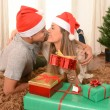 Young Happy Couple Kissing on rug at Christmas — Stock Photo #35082327